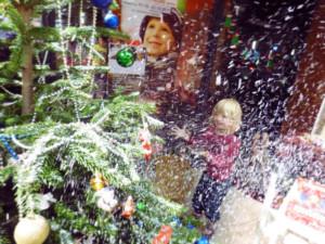 Kind freut sich über Schnee mit Tannenbaum vor dem FairKaufhaus zur Kinderträume Weihnachtsaktion